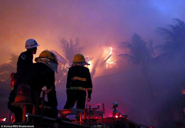 El humo seguía saliendo de los restos de la construcción junto a un lago horas después del amanecer. (Foto de Xinhua)
