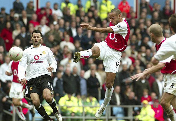 En foto del 3 de abril de 2004 se muestra el momento exacto en que Thierry Henry, que había entrado de cambio, patea la pelota para anotar a favor del Arsenal en la semifinal contra Manchester United. (Foto: AP)