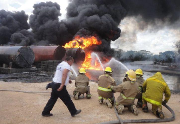 Bomberos combaten el incendio en el depósito clandestino de aceites y combustibles, en la carretera Umán-Poxilá. (SIPSE)