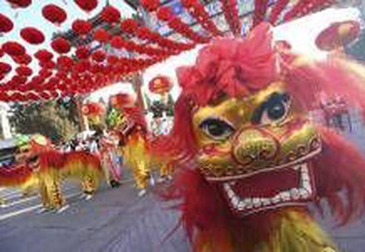 China recibe al 'mono de fuego' con la esperanza de que traiga buena fortuna. Artistas chinos interpretan el baile del león en el parque Ditan durante el primer día del Año Nuevo Lunar, en Beijing. (EFE)