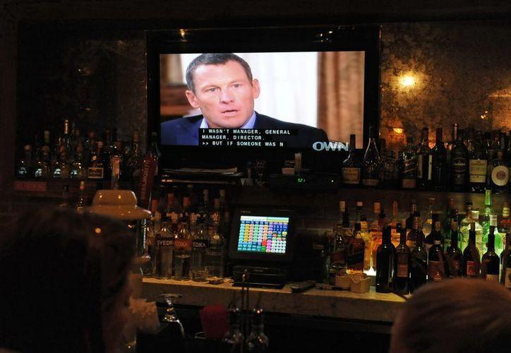 Varios clientes en un restaurante deNueva York (EU.) observan la transmisión de la entrevista exclusiva de la presentadora Oprah Winfrey al exciclista estadounidense Lance Amstrong. (EFE/Archivo)