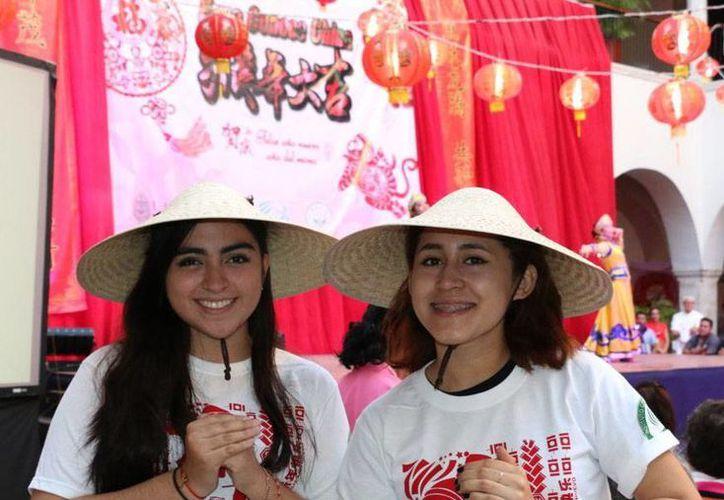 Samanta Sobrino Bermejo y Wendy Mendoza Vázquez, estudiantes del Instituto Confucio de la Uady, en la decimotercera Expo Conoce China, ayer sábado en el edificio central de la casa de estudios. (Prensa Uady)