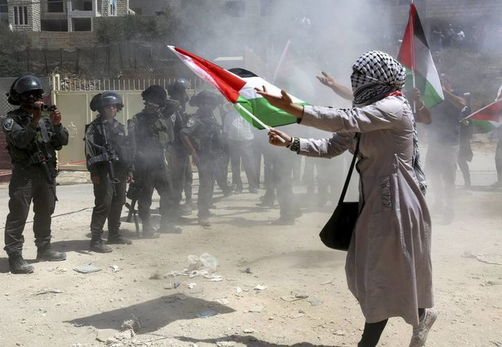 Una mujer palestina ondea una bandera durante los enfrentamientos entre la policía israelí y manifestantes palestinos, los cuales se suscitaron después de la misa dominical. (EFE)