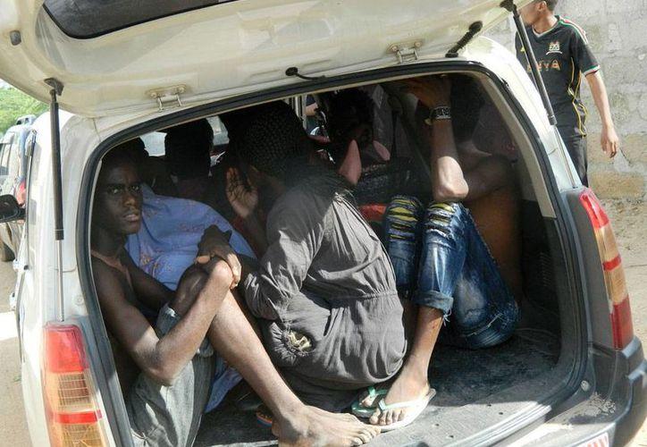 Estudiantes del colegio universitario de Garissa se refugian en un auto del ataque de hombres armados a las instalaciones del colegio, el 2 de abril de 2015. (Foto AP)