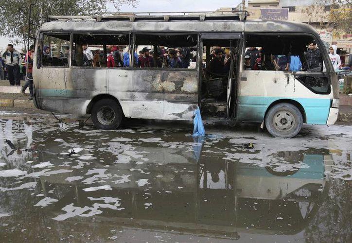 Numerosos curiosos observan los destrozos causados por la explosión de una camioneta cargada de explosivos en un concurrido mercado al aire libre en el distrito de Ciudad Sadr en el este de Bagdad. (AP/Karim Kadim)