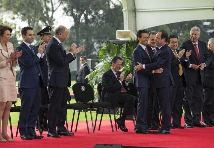Abrazo entre los presidentes de Francia y México durante la recepción oficial del primero en el Campo Marte. (presidencia.gob,mx)
