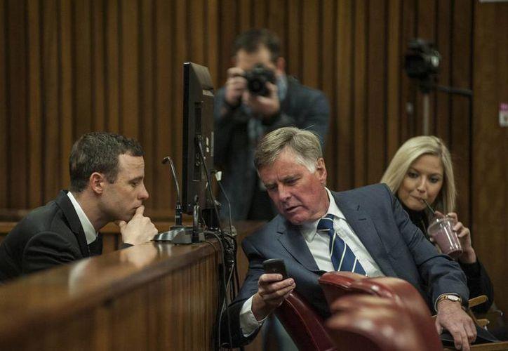Pistorius (i) dialoga con un integrante de su defensa en el juicio que se le sigue desde el año pasado por el crimen de su novia, muerta a balazos. (Foto: AP)