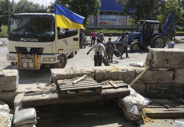 Ucranianos deconstruyen una barricada de militares prorrusos, que huyeron de Slaviansk y Kramatorsk a Donetsk, en Slaviansk, Ucrania. (EFE)