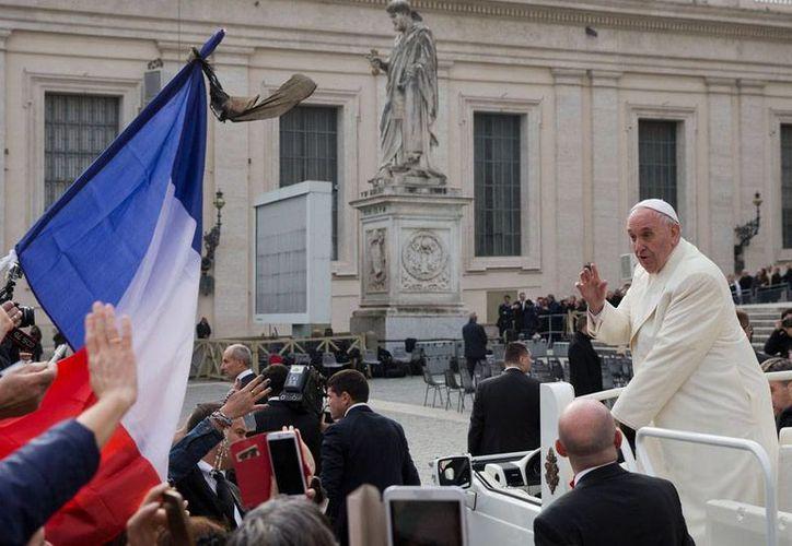 El Papa Francisco saluda a un grupo de fieles que ondea una bandera de Francia, a su arribo a la Plaza de San Pedro, en El Vaticano, para su audiencia del miércoles 18 de noviembre de 2015. (Foto:AP/Andrew Medichini)