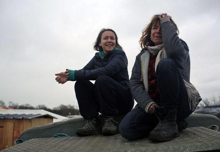 Imagen del 4 de febrero de 2016 en que se ve a la voluntaria Liz Clegg (d) junto a su hija Inca Sorrell en un campamento de migrantes de Calais, Francia. Clegg recibió el mensaje de texto de un niño afgano que permitió rescatar a 15 migrantes en Inglaterra. (AP Foto/Thibault Camus)