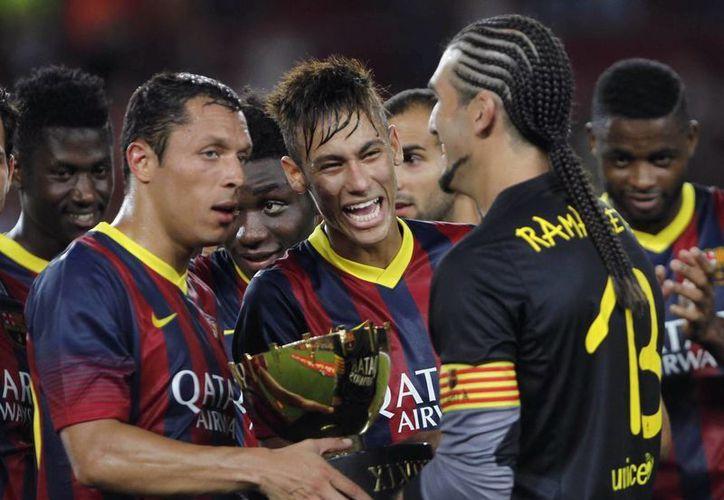 Los jugadores del Barcelona, Pinto (d), y los brasileños Neymar (c) y Adriano, posan con el trofeo tras vencer al Santos FC. (EFE)