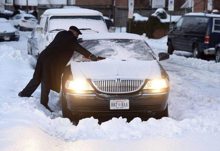 """Un hombre quita la nieve de su coche en una calle de Alexandria, Virginia, E.U., una de las zonas afectadas por la tormenta invernal """"Pax"""", que ahora vira hacia el noroeste de Estados Unidos. (EFE)"""