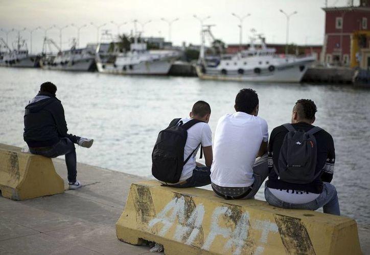 Los menores egipcios que viajan solos (de izquierda a derecha) Fathi, de 16 años y Saied, Gamal y Ayman, todos de 17 años, cuyos apellidos no estuvieron disponibles, sentados a orillas del río Tíber tras una entrevista con The Associated Press, en Fiumicino, al oeste de Roma. (Agencias)