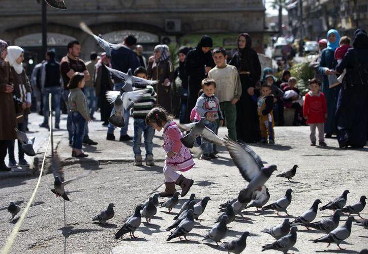 Siria vive una  relativa calma que no se había visto en años tras el cese al fuego declarado este viernes. En imagen se aprecia gente en una plaza de Damasco, capital del país asiático. (Imágenes de AP)