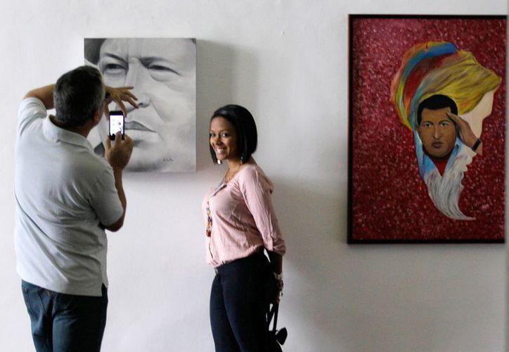 Una visitante posa junto a un retrato del presidente venezolano Hugo Chávez en la exposición pictórica. (Agencias)