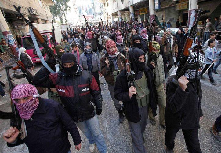 Un grupo de rebeldes caminan por las calles de Siria, donde la 'guerra civil' ha cobrado miles de vidas. (Archivo/Agencias)