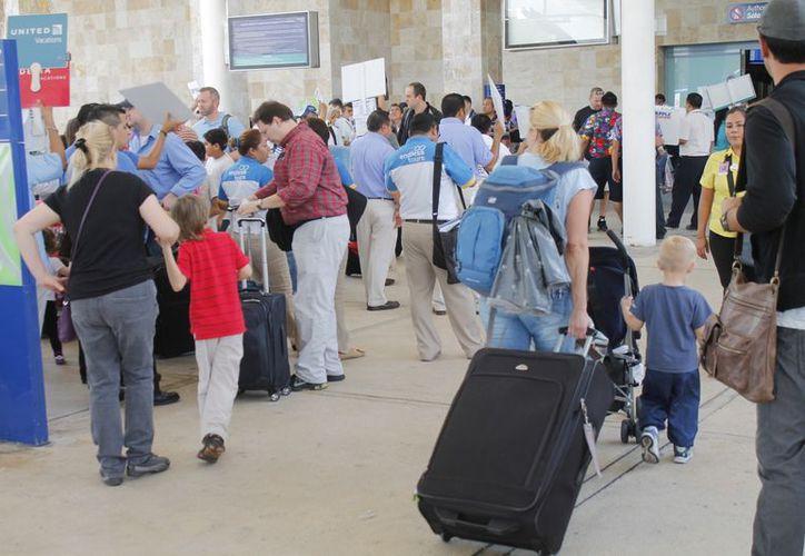 La terminal aérea lució ayer abarrotada de turistas nacionales e internacionales. (Jesús Tijerina/SIPSE)