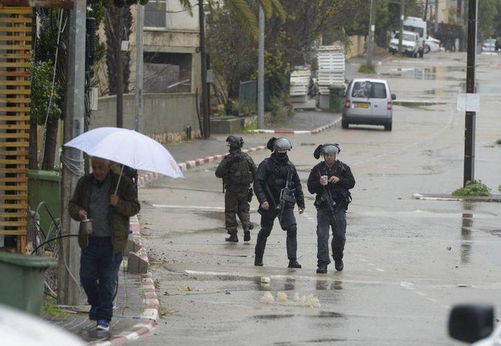 Policías israelíes patrullan las calles de el pueblo arabe-israelí de Arara, al norte de Israel durante una operación de búsqueda de Nashat Melhem supuesto autor de la muerte de tres israelíes en Tel Aviv el pasado 1 de enero. (EFE)