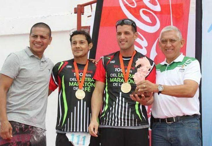 El ganador del Ultra Maratón, el boricua Jerjes Aquino, el segundo lugar, el español Gerónimo Montero, acompañados del ex campeón mundial pluma Guty Espadas Jr. y el director del IDEY, Juan Sosa Puerto. (Milenio Novedades)