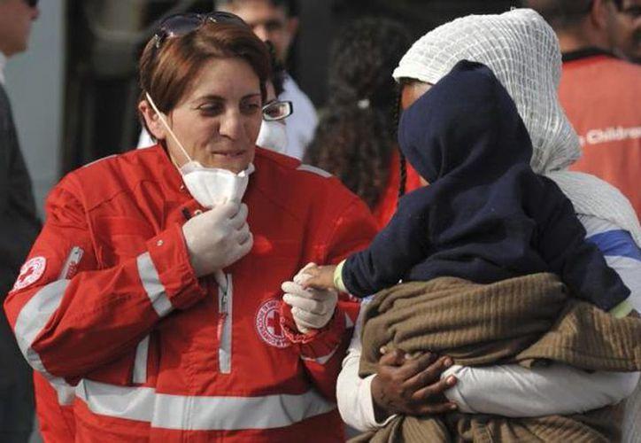 Inmigrantes desembarcan en el aeropuerto Catania de Sicilia, Italia, el jueves 14 de mayo de 2015. (Foto AP/Carmelo Imbesi)