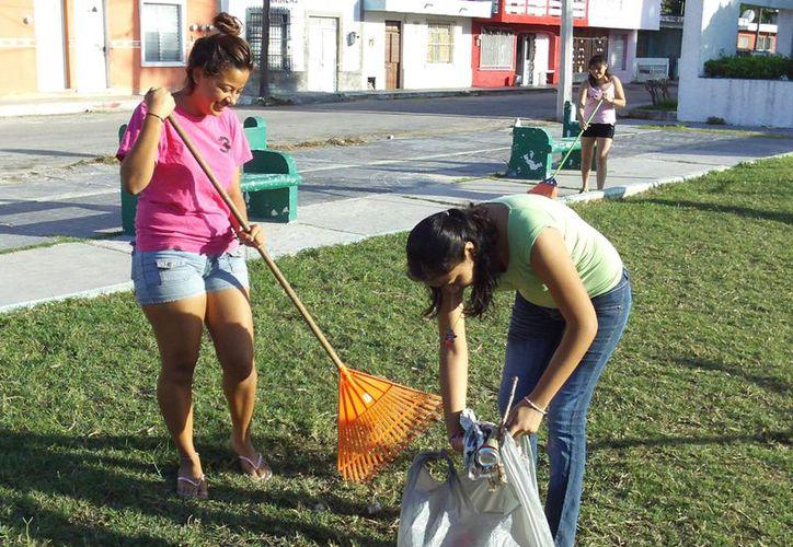 Diana Villicaña, Blanca Pool y Arletti López, recogieron la basura del parque infantil ubicado detrás de la Dirección de Ecología. (Manuel Pool/SIPSE)