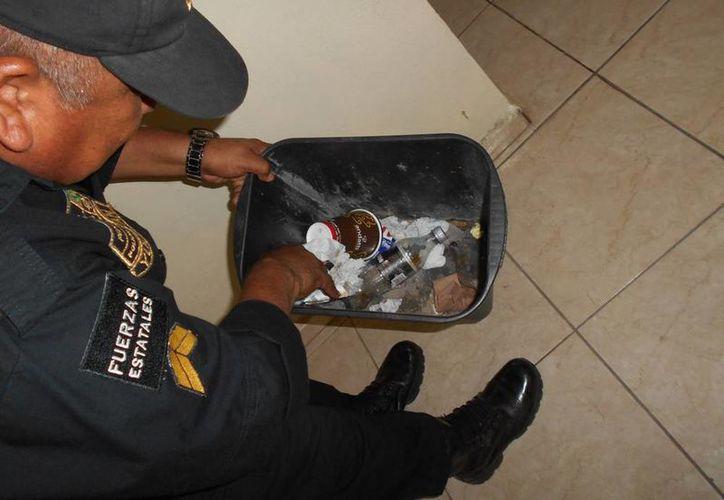 Un policía revisar el bote de basura en donde una abogado echó una extraña sustancia que causó una epidemia de estornudos, en un juzgado de Mérida. (Francisco Puerto/SIPSE)