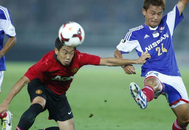 Un japonés disputa el balón contra otro japonés. Nada más que uno juega para el Manchester United (Kagawa-i) y el otro para el Yokohama (Narawa-d). (Agencias)
