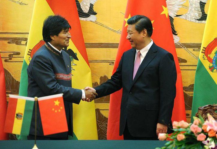 El presidente boliviano, Evo Morales (izq) estrecha la mano del presidente de China, Xi Jinping, durante una ceremonia de firma en el Gran Palacio del Pueblo en Beijing. (Agencias)