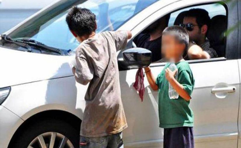 De limpiaparabrisas es como se emplean algunos niños en los diferentes cruceros de la ciudad. (Milenio Novedades)