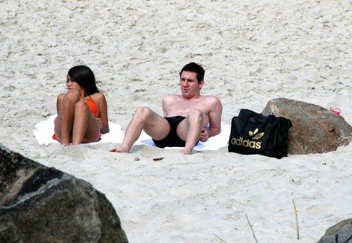 Tras la hospitalización de su mujer, Messi disfruta de vacaciones en el Caribe, en la imagen se observa al argentino tomar el sol al lado de su mujer Antonella Rocuzzo. (EFE)