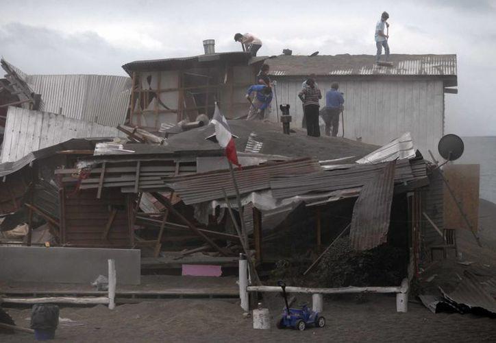 Habitantes de un predio en Puerto Varas, Chile, limpian su hogar de la ceniza expulsada por el volcán Cabulco y que amenaza con ser más peligrosa y pesada con la lluvia pronosticada. (Foto: AP)