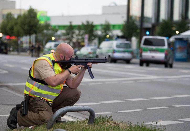 Un agente apunta su arma hacia el centro comercial de Munich donde poco antes un sujeto solitario mató a nueve personas e hirió a otras 16 en un tiroteo. (AP)