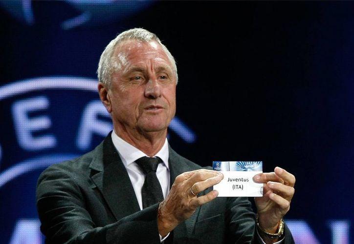 """Johan Cruyff saca la papeleta de Juventus durante el sorteo de la Liga de Campeones el 29 de agosto del 2013 en Mónaco. El holandés, pilar de un equipo naranja que revolucionó el deporte con su concepto de """"fútbol total"""", falleció el 24 de marzo del 2016 a los 68 años. (AP Photo/Claude Paris)"""
