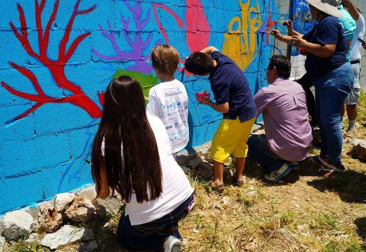 En la avenida Huayacán, a unos metros de la avenida Kabáh, pintan el mural. (Redacción/SIPSE)