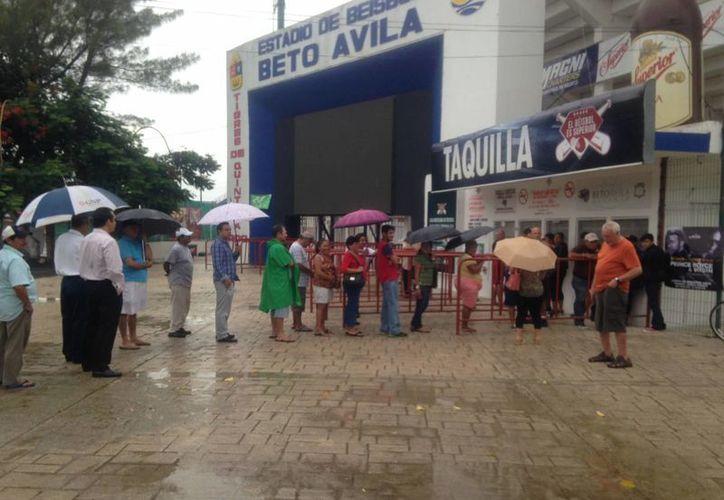 Los aficionados de los Tigres de Quintana Roo acudieron al estadio, pese a la lluvia, para comprar sus boletos para el sexto juego. (Redacción/SIPSE)