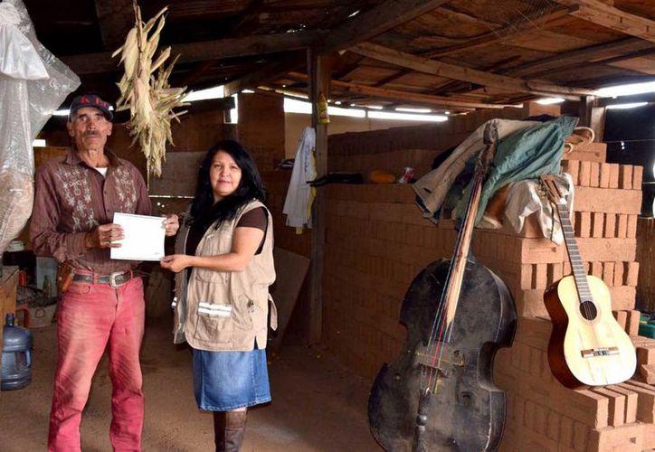 Hermelindo y su esposa Gloria muestran uno de los certificados de Primaria que recién obtuvieron, tras brindarles estudios universitarios a sus ocho hijos. (Notimex)