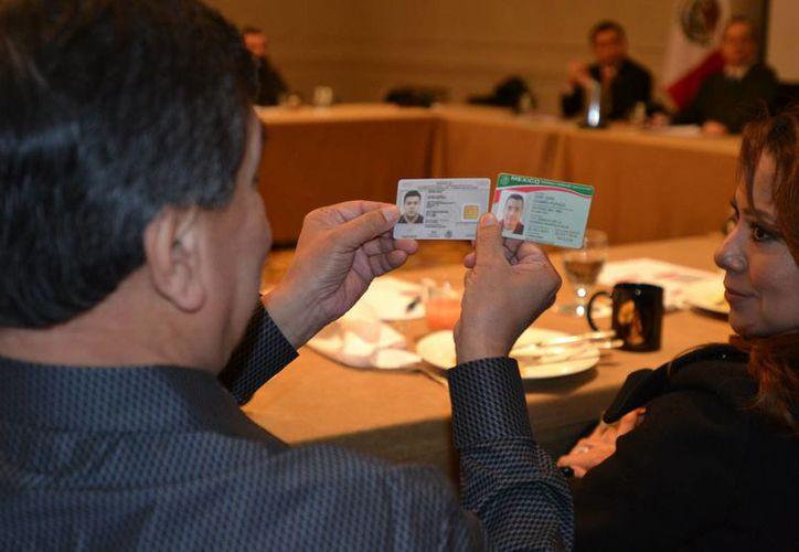 Un asistente a la conferencia de prensa del Consulado General de México en Chicago observa las dos matrículas consulares, la nueva (izda) y la antigua (dcha). (EFE)