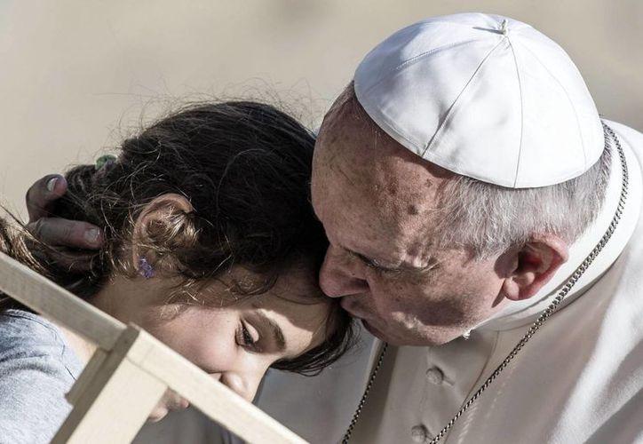 El Papa besa a una niña durante su visita a la Iglesia Santa María Regina Pacis en Ostia. (EFE)