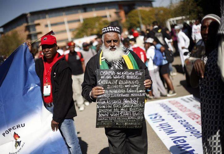 """Un hombre sostiene un letrero que llama al presidente Obama """"el ayudante de la Casa Blanca"""" y expresa muchas cosas que cree que están mal con la política exterior de Estados Unidos. (Agencias)"""