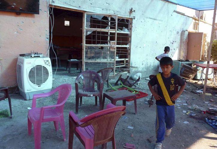 Niños iraquíes en una cafetería destruida tras un bombazo en Tunis, al norte de Bagdad. (EFE/Archivo)