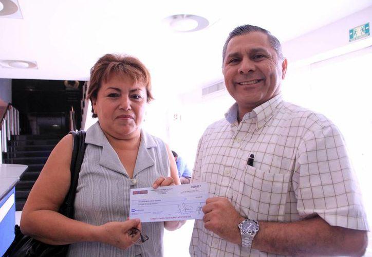 El director regional de Circulación de Medios Impresos de Grupo SIPSE, José Luis Valladares entrega el cheque a doña Lilia. (SIPSE)