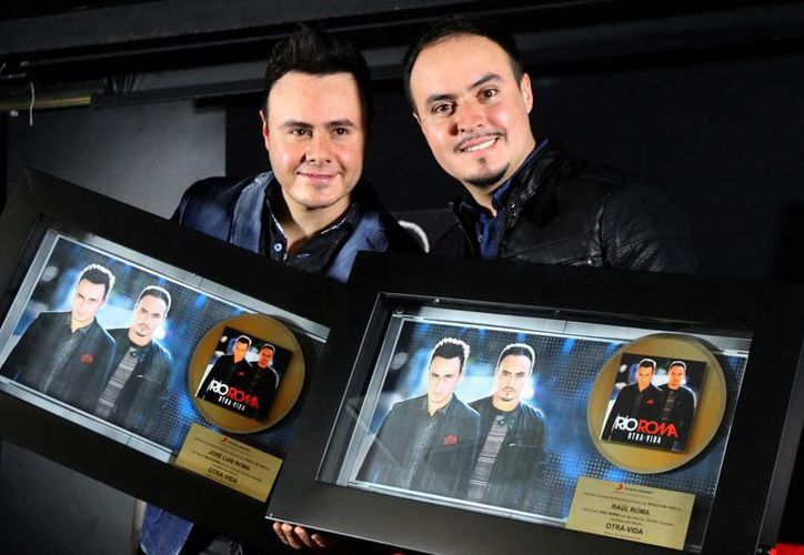 """Raúl y José Luis Ortega Castro, integrantes de Río Roma, lucen el Disco de Oro que recibieron por sus altas ventas del álbum """"Otra vida"""". (Notimex)"""
