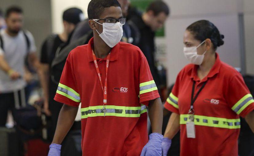 Los empleados del aeropuerto usan máscaras como precaución contra la propagación del nuevo coronavirus COVID-19 mientras trabajan en el Aeropuerto Internacional de Sao Paulo en Brasil. (Foto: AP).