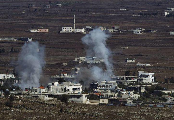 Columnas de humo se elevan entre varias residencias de la aldea de el-Hmidaiah junto a la frontera Siria, en Quneitra, Israel. (Archiovo/EFE)