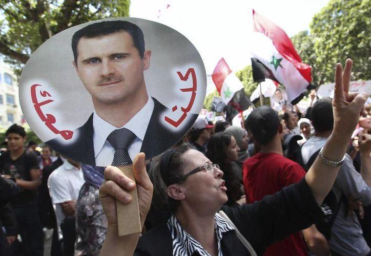 Una simpatizante de Bachar al Asad muestra una pancarta con el rostro del presidente sirio, durante una manifestación en Túnez. (Archivo/EFE)