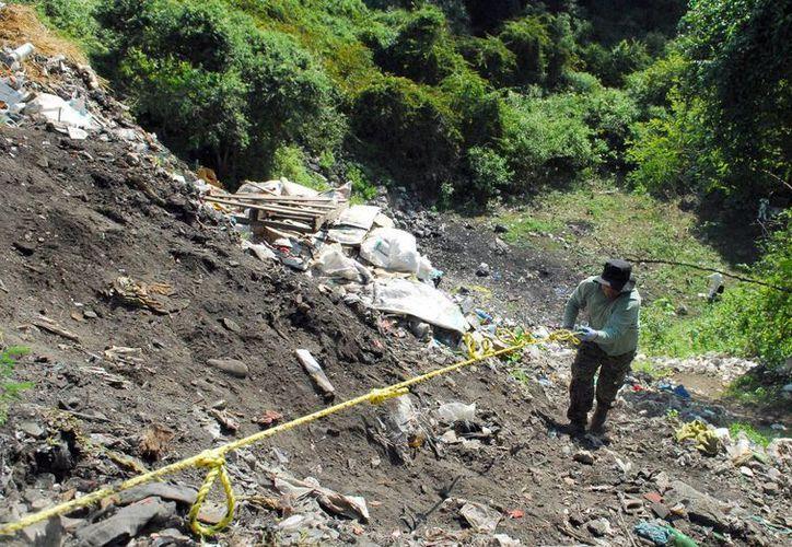Imagen de archivo de uno de los peritos de la PGR que investigaban en el basurero municipal de Cocula, para tratar de encontrar indicios sobre el caso Ayotzinapa. (Archivo/Notimex)