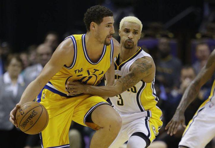 El guardia de Indiana Pacers, George Hill (3) enfrenta a Klay Thompson (11), de Golden State Warriors. Este último equipo ganó y llegó a 27 triunfos al hilo en la NBA, un récord. (AP)
