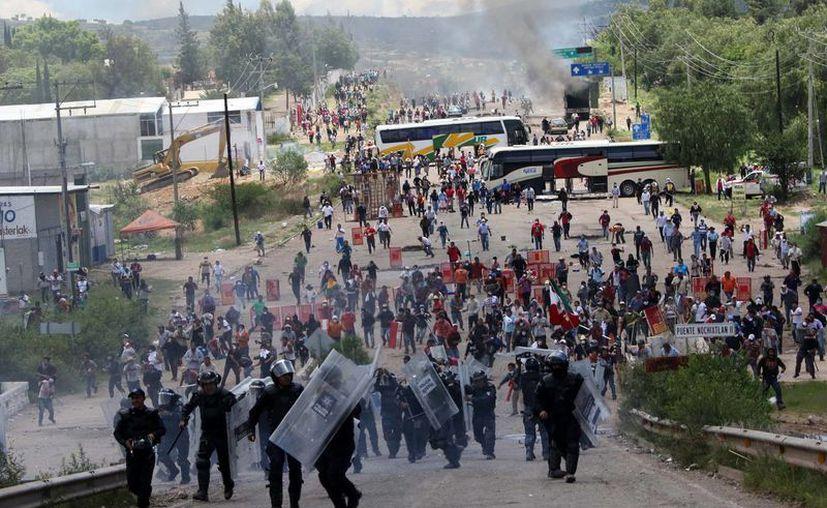 Los profesores han mantenido plantones, marchas y bloqueos durante las últimas semanas en Oaxaca. Imagen de archivo del enfrentamiento que hubo en Nochixtlán. (Agencias)