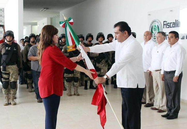 Víctor Caballero Durán, secretario general de Gobierno, al hacer entrega del pabellón nacional a la fiscal estatal Celia Rivas Rodríguez. (Milenio Novedades)