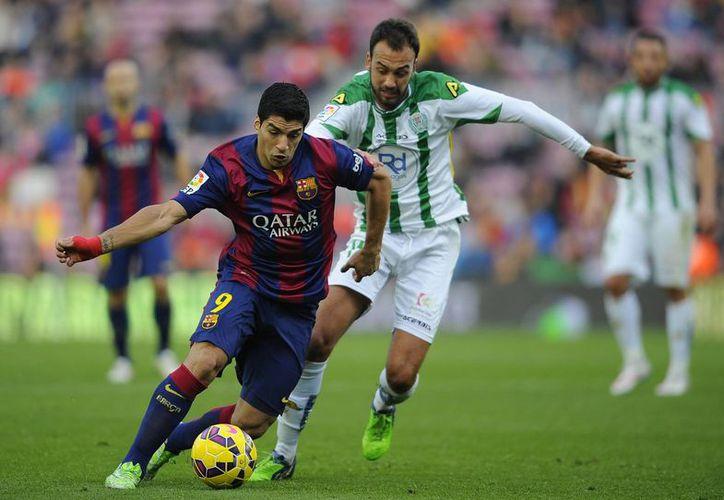 Luis Suárez, del equipo Barcelona, se encarrila con peligro al marco del Córdoba, pese a la marca de Deivid Rodríguez. (Foto:AP)